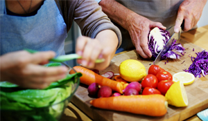 Picture of a Couple Chopping Vegetables